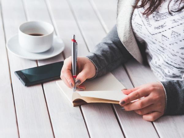 7 dicas para emagrecer sem sofrer - Mulher escrevendo num caderno de anotações
